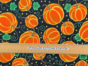 Ruler on black cotton fabric that is covered with orange pumpkins, green swirls and leaves and yellow stars.