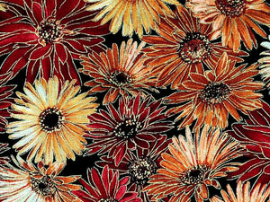 Close up of black cotton fabric that is covered with mums in shades of orange and peach.