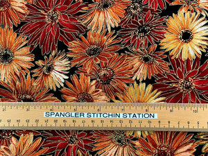 Ruler on black fabric that is covered with mums in shades of orange and peach.