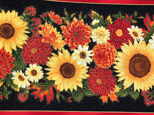 Close up of black cotton fabric covered with fall flowers such as mums.