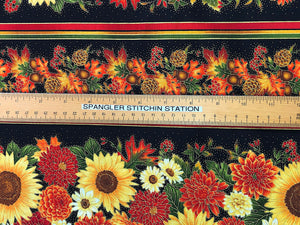 Ruler on black cotton fabric covered with rows of fall flowers, leaves and pinecones.