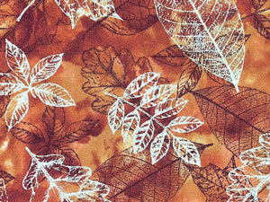 Close up of cotton fabric covered with metallic leaves.
