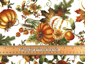 Ruler on white cotton fabric that is covered with pumpkins, leaves, gourds and pinecones.