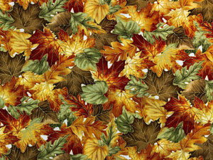 Close up of cotton fabric covered in orange, brown and green leaves.