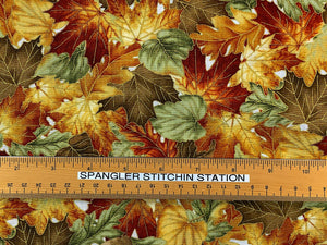 Ruler on cotton fabric that is covered in orange, green and brown leaves.