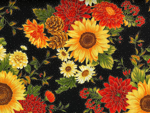 Close up of black cotton fabric that is covered with fall flowers.