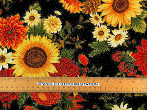 Ruler on black cotton fabric that is covered with fall flowers.