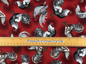 Ruler on burgundy cotton fabric that is covered with french chickens.