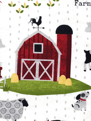 Close up of white cotton fabric with farm animals and barns.