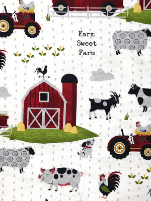 Close up of white cotton fabric that is covered with farm animals, barns and tractors.