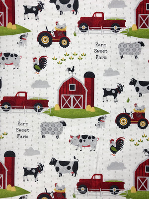 White cotton fabric covered with barns, cows, sheep, pigs, tractors and more.