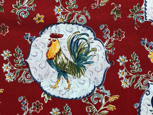 Close up of rooster on red fabric surrounded by flowers.