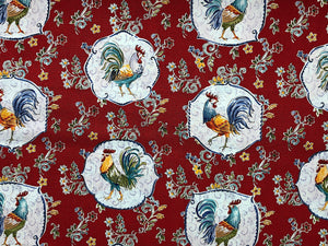 Red cotton fabric covered with roosters and flowers.