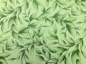 Close up of light green cotton fabric covered with green leaves and branches.