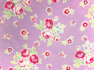 Close up of lavender cotton fabric covered with pink roses and green leaves.
