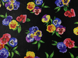 Close up of black fabric that is covered with pansies.