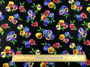 Ruler on black fabric that is covered with pansies.