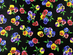 Black cotton fabric covered with pansies.