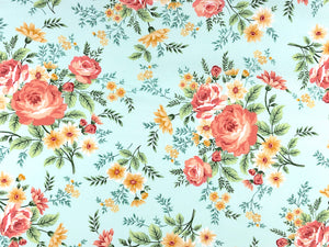 Light green cotton fabric covered with roses and other flowers.