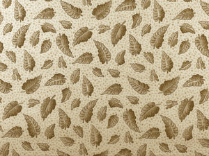 Cream Cotton Fabric covered with leaves in shades of brown.