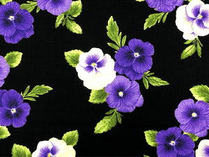 Close up of black cotton fabric that is covered with purple and yellow pansies.