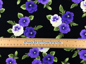 Ruler on black cotton fabric that is covered with purple and yellow pansies