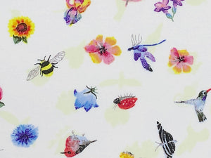 Close up of white cotton fabric that is covered with small flowers, bees, birds and hummingbirds.