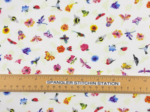 Ruler on white cotton fabric that is covered with small butterflies, hummingbirds, bees, birds and flowers.