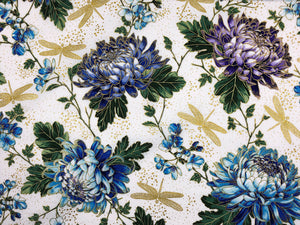 White cotton fabric covered with blue and purple hydrangeas and gold dragonflies.