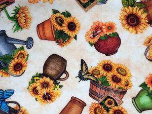 Close up of cream fabric covered with pots of sunflowers and butterflies.