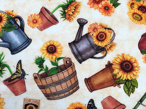 Close up of sunflowers in watering cans and flower pots.