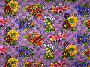 Cotton fabric covered with sunflowers, lilies and other flowers.