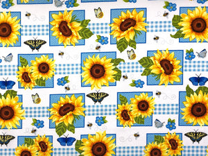 Cotton fabric covered with sunflowers, bees, butterflies and small blue flowers.