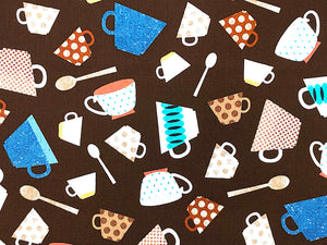 Close up of brown cotton fabric that is covered with cups and spoons.