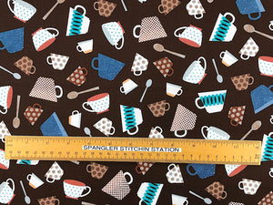 Ruler on brown cotton fabric that is covered with cups and spoons.