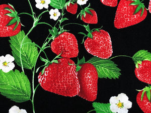 Close up of black cotton fabric covered with red strawberries, white flowers and green leaves.