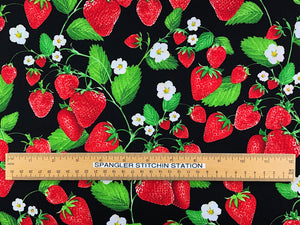 Ruler on fabric to show sizing of strawberries and leaves.