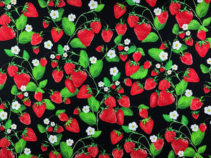 Black cotton fabric covered with red strawberries, white flowers and green leaves.