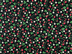 Black cotton fabric covered with small strawberries, white flowers and green leaves.