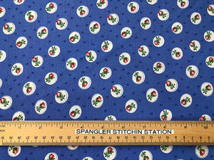 Ruler on blue fabric that is covered with rose buds.