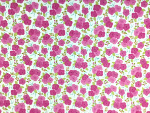 Cotton fabric covered with pink hibiscus and green leaves.