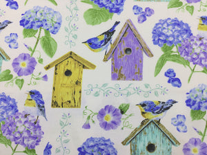 Close up of white fabric covered with hydrangeas, and bird houses.