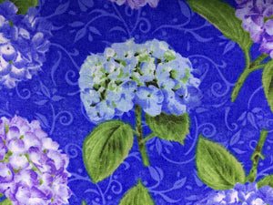 Close up of blue hydrangea and green leaves.