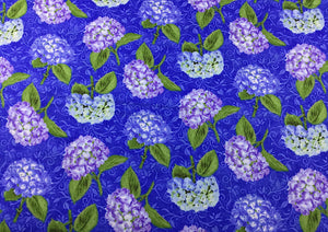 Blue cotton fabric covered with blue and purple hydrangeas and green leaves.