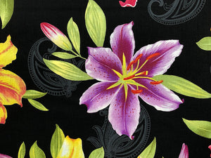 Close up of black fabric that has a purple lily on it.