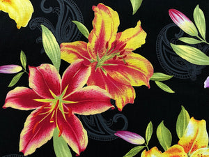 Close up of black cotton fabric with yellow and red lilies.