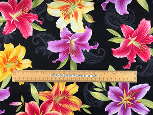 Ruler on black fabric that is covered with yellow, red and purple lilies.