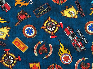 Close up of navy fabric covered with firetrucks and shields.