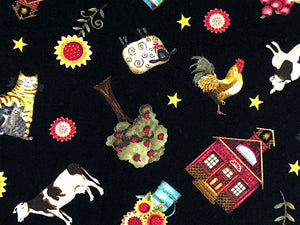 Close up of cotton fabric that is covered with cows, sheep, cats, flowers and houses.