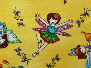 Close up of yellow fabric covered with fairies.